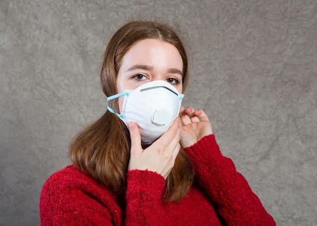 Vorderansicht der frau, die eine medizinische maske auf gesicht zum schutz trägt