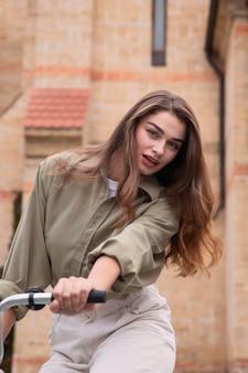 Vorderansicht der frau, die fahrrad in der stadt reitet