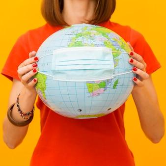 Vorderansicht der frau, die globus mit medizinischer maske hält