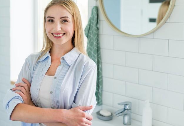 Vorderansicht der frau, die im badezimmer mit toilettenartikeln aufwirft