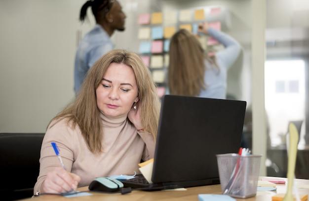 Vorderansicht der frau, die im büro arbeitet