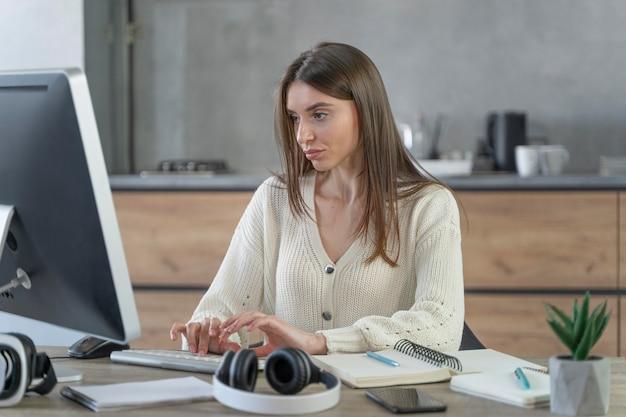Vorderansicht der frau, die im medienfeld mit personal computer arbeitet