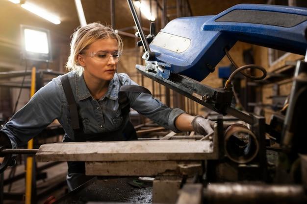 Vorderansicht der frau, die in der fabrik arbeitet