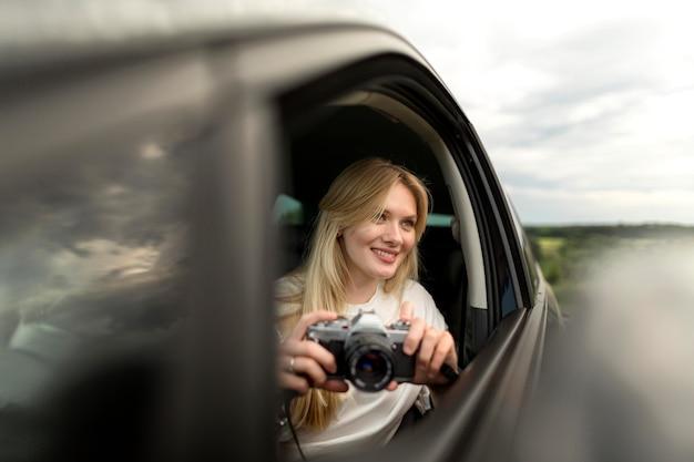 Vorderansicht der frau, die kamera im auto hält