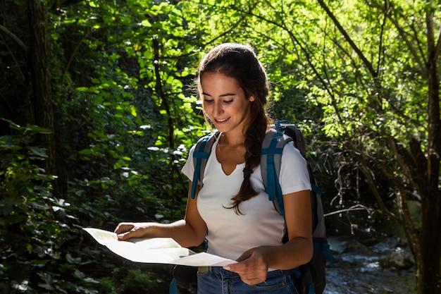 Vorderansicht der frau, die karte hält und natur erforscht
