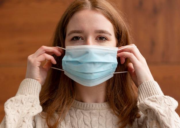Vorderansicht der frau, die medizinische maske aufsetzt