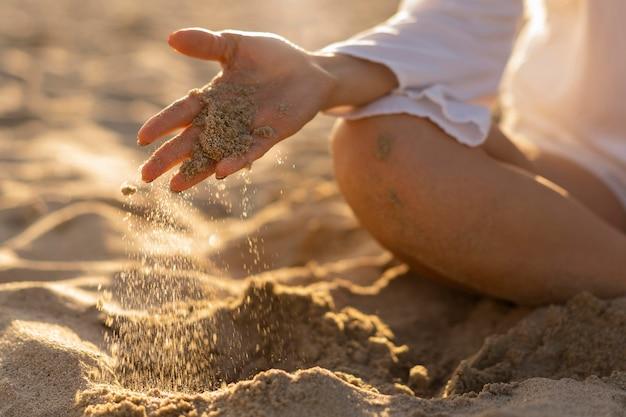 Vorderansicht der frau, die mit strandsand spielt