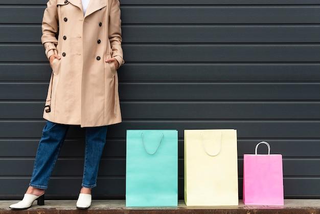 Vorderansicht der frau, die neben einkaufstaschen unterschiedlicher größe aufwirft