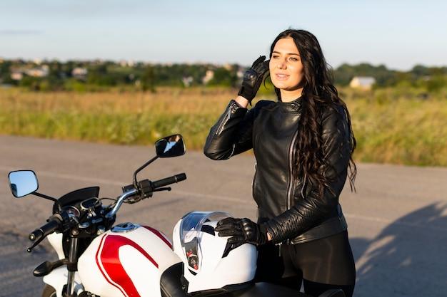 Vorderansicht der frau, die neben ihrem motorrad im sonnenuntergang aufwirft