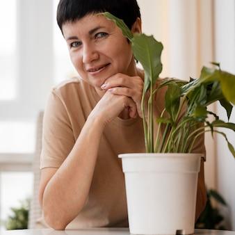 Vorderansicht der frau, die neben zimmerpflanze aufwirft