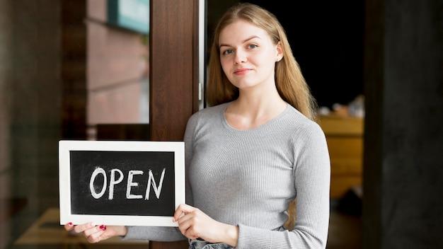 Vorderansicht der frau, die offenes zeichen für coffeeshop hält