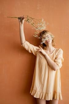 Vorderansicht der frau, die schöne frühlingsblumen hält