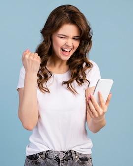Vorderansicht der frau, die siegreich ist, während sie smartphone hält