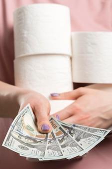 Vorderansicht der frau, die toilettenpapierrollen hält und geld übergibt