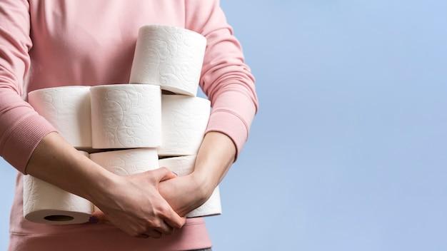 Vorderansicht der frau, die viele toilettenpapierrollen mit kopienraum hält