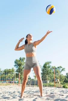 Vorderansicht der frau, die volleyball am strand spielt