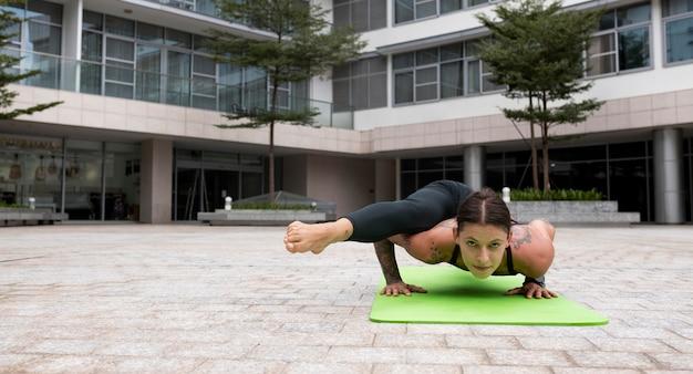 Vorderansicht der frau, die yoga auf matte praktiziert