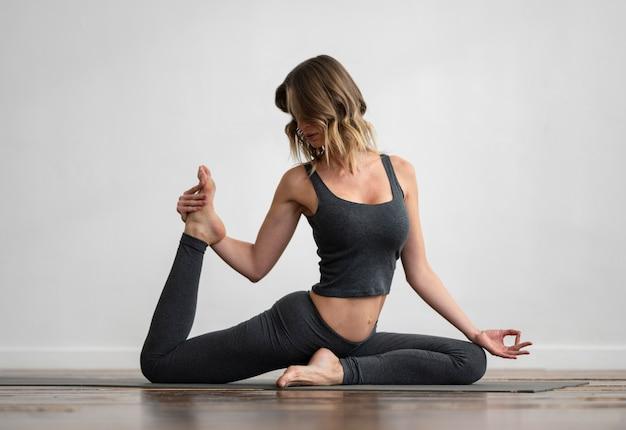 Vorderansicht der frau, die yoga zu hause auf matte tut