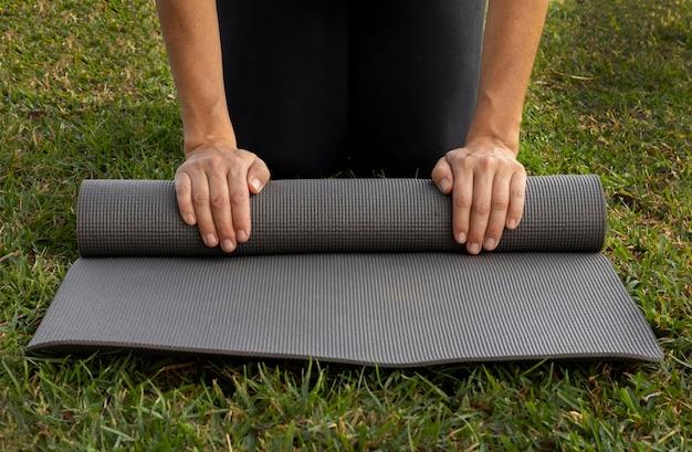 Vorderansicht der frau, die yogamatte auf dem gras rollt
