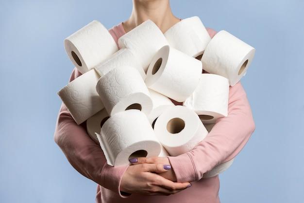 Vorderansicht der frau, die zu viele toilettenpapierrollen hält