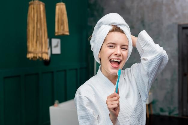 Vorderansicht der frau im bademantel singend in der zahnbürste