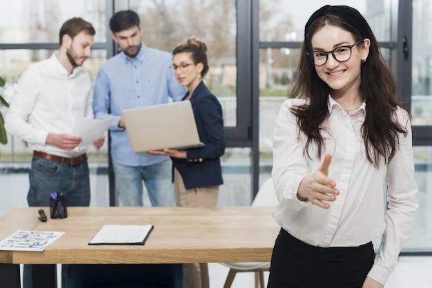 Vorderansicht der frau im büro, die händedruck anbietet