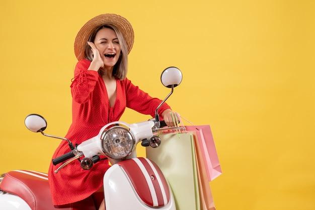 Vorderansicht der frau im roten kleid auf moped, das einkaufstaschen hält
