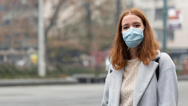 Vorderansicht der frau in der stadt, die medizinische maske mit kopienraum trägt