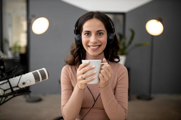 Vorderansicht der frau in einem radiostudio mit mikrofon und kaffee