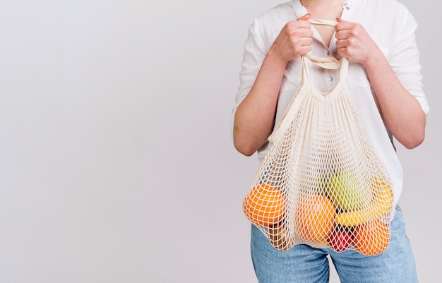 Vorderansicht der frau mit beutel der früchte