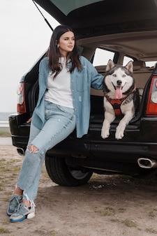 Vorderansicht der frau mit dem husky-hund, der mit dem auto reist