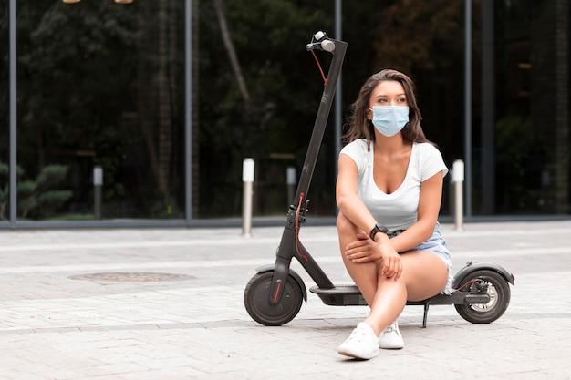 Vorderansicht der frau mit der medizinischen maske, die auf elektroroller sitzt