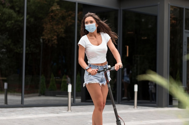 Vorderansicht der frau mit der medizinischen maske, die einen elektroroller reitet