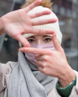 Vorderansicht der frau mit der medizinischen maske, die rahmen mit händen macht