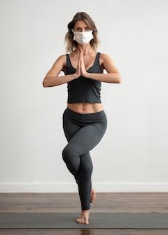 Vorderansicht der frau mit der medizinischen maske, die yoga tut