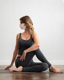 Vorderansicht der frau mit der medizinischen maske, die yoga zu hause tut