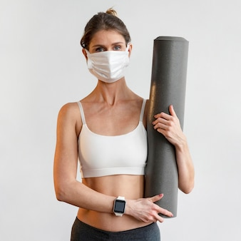 Vorderansicht der frau mit der medizinischen maske, die yogamatte hält