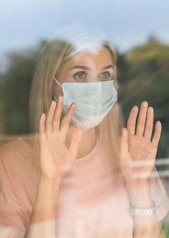 Vorderansicht der frau mit der medizinischen maske zu hause, die fenster während der pandemie berührt