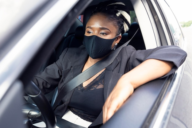 Vorderansicht der frau mit gesichtsmaske, die ihr auto fährt
