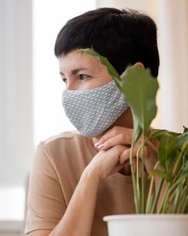 Vorderansicht der frau mit gesichtsmaske, die neben zimmerpflanze aufwirft