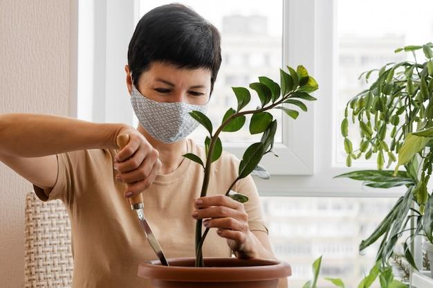 Vorderansicht der frau mit gesichtsmaske, die sich um zimmerpflanze im topf kümmert