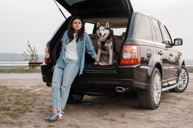Vorderansicht der frau mit husky, der zusammen mit dem auto reist