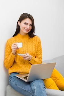 Vorderansicht der frau mit laptop auf dem schoss, der tasse kaffee hält