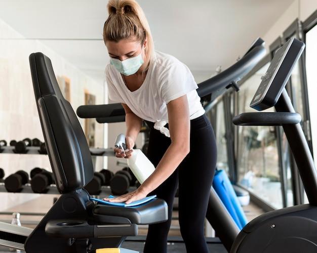 Vorderansicht der frau mit medizinischer maske, die fitnessgeräte reinigt