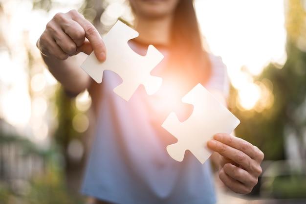 Vorderansicht der frau puzzlespielstücke halten