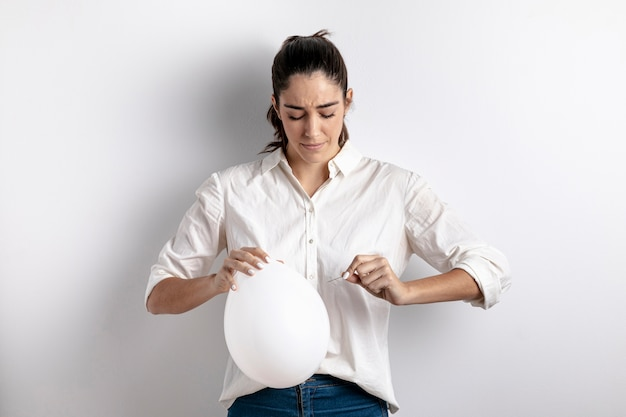 Vorderansicht der frau versuchend, einen ballon zu knallen