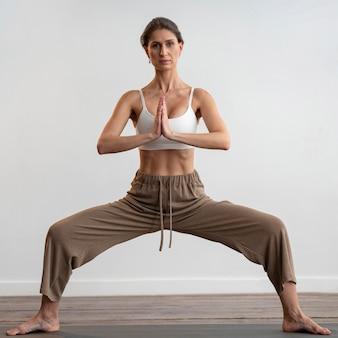 Vorderansicht der frau zu hause, die yoga praktiziert