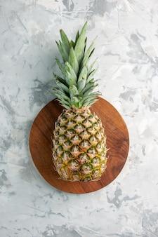 Vorderansicht der ganzen frischen goldenen ananas auf schneidebrett auf marmoroberfläche
