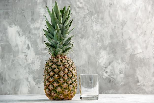 Vorderansicht der ganzen frischen goldenen ananas und des glases auf dem tisch
