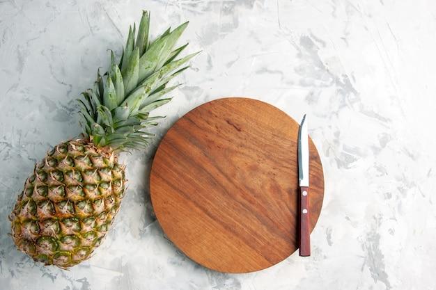 Vorderansicht der ganzen frischen goldenen ananas und des schneidebrettmessers auf der tischmarmoroberfläche